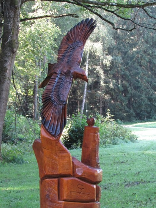 Sculpture of a bird of prey among the park