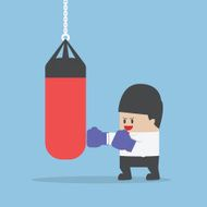 Businessman wearing boxing gloves and punch the punching bag