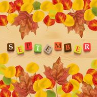 "Autumn background with leaves and colorful letters ""september"""