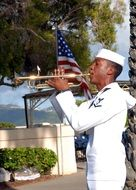 black trumpeter in white uniform playing outside