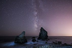 milky way boulders sea beach stars night