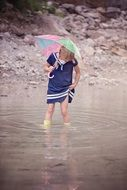 girl in blue dress with umbrella water