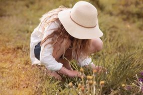Blonde Girl in white hat takes flowers