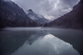mountains near the lake in the fog