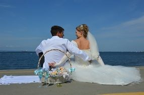 wedding couple sit on beach in front of sea
