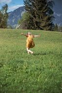 the child runs through a green meadow