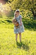 Little girl with a plush toy on the nature