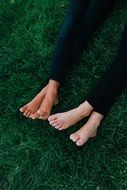 Friends feet on green grass