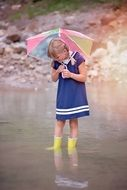 girl in rubber boots and umbrella