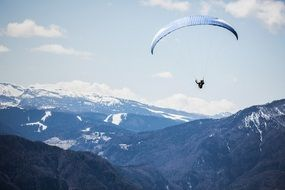 skydiver over snowy mountains