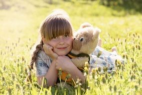 girl is hugging a teddy bear in a meadow