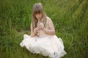 girl in white dress playing the flute in nature