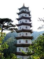 white tower of a buddhist temple among green trees