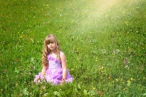 Little girl in a beautiful dress with long hair amid the meadow in the sun