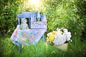 child castle on table in green grass daisies
