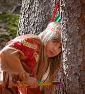 blond child girl's face among trees