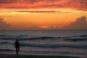 silhouette of a surfer on the beach at sunrise
