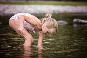 Little girl in a swimsuit plays in the water of a lake