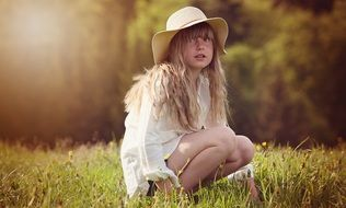 Little girl with long curly hair and a hat in the meadow