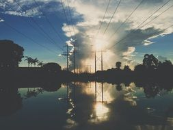 landscape of power lines are reflected in the water at dusk