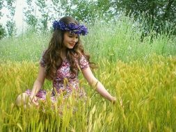 girl with a purple wreath on her head in the field