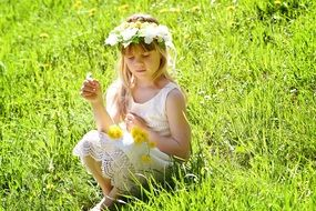 long hair blond girl child playing with flowers