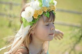 Little girl in wreath with eyes closed