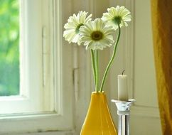 daisies in a yellow vase in the house