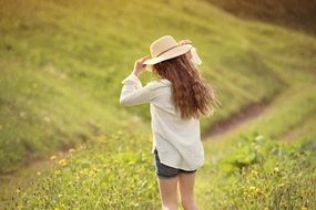 blonde girl in white hat in field back view