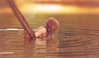 Little girl with long hair in the lake