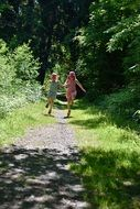 Two little girls running around the forest trail
