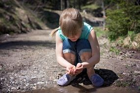 blonde girl sitting near puddle
