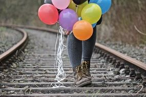 child with balloons on the rails