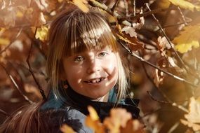 smiling blonde girl face in autumn tree leaves