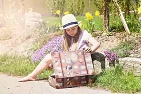 Picture of girl with luggage in a garden