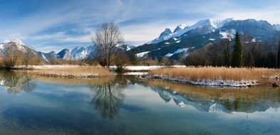alpine mountains are reflected in the water