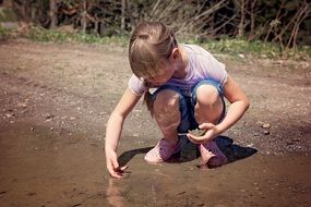 blonde girl sitting in water puddle