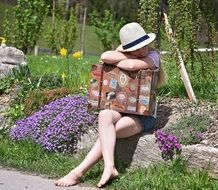 Girl sitting with suitcase in the garden with colorful flowers