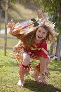 Little girl in an Indian costume playing with a tomahawk