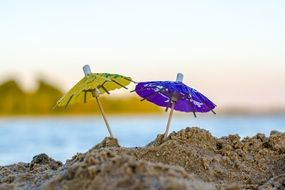 two cocktail umbrellas on the beach