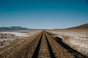 Beautiful railway tracks in sunny desert under blue and white sky background