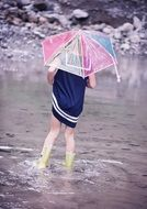 girl in a blue dress with an umbrella and in rubber boots