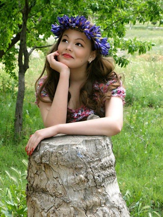 beautiful girl with a wreath of flowers on her head outdoors