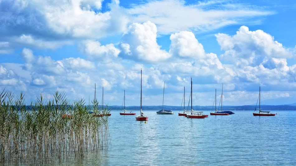 anchored sailing boats on chiemsee lake beneath scenic clouds, germany, upper bavaria