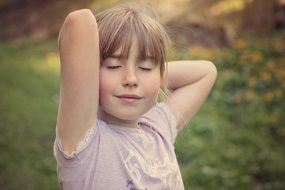 Little girl in relaxed pose outdoors