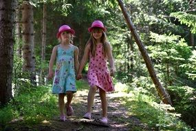 Little girls in pink hats in the middle of the forest