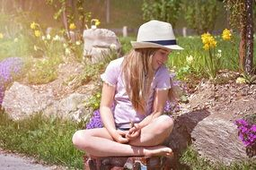 happy barefeet child girl sits on luggage in garden
