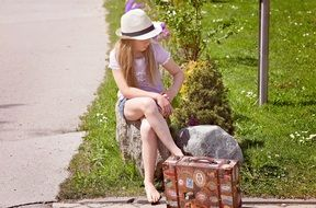 girl in hat sitting on stone with suitcase