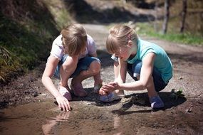 Blonde girls playing in puddle