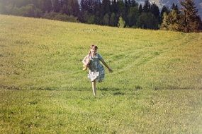 little girl running on green grass